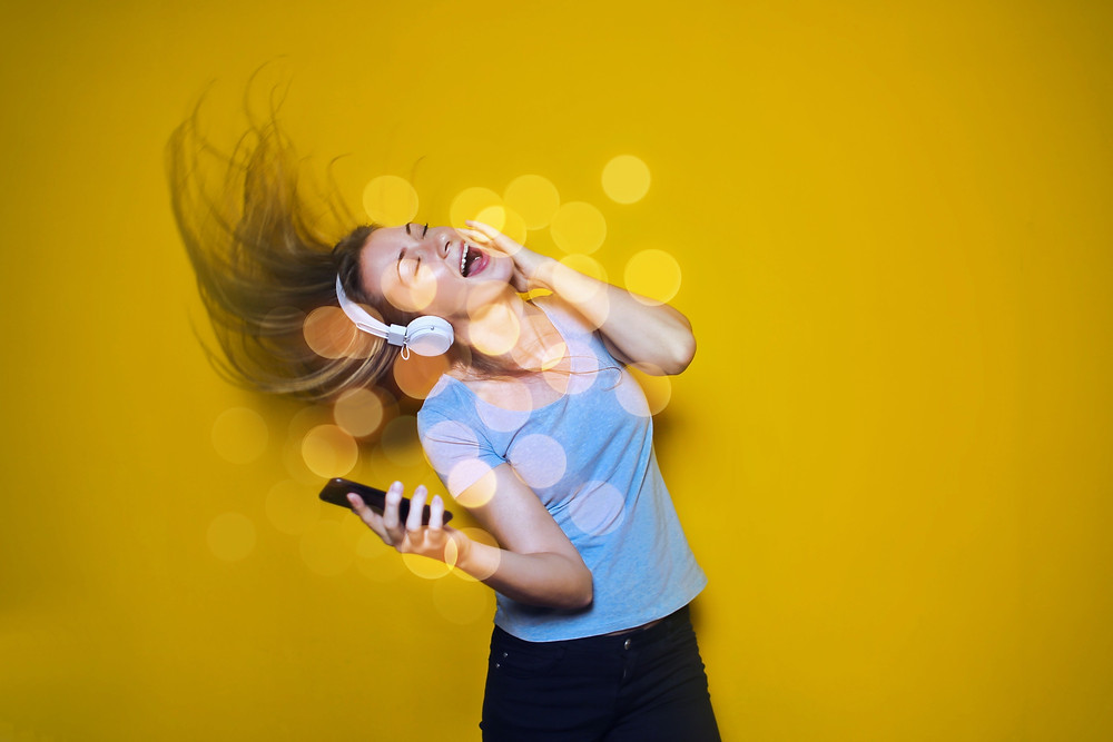 Woman with headphones singing and waving her hair in joy, practicing self care