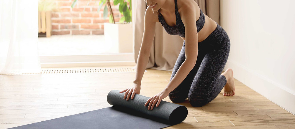 Woman smiling and rolling out a yoga mat