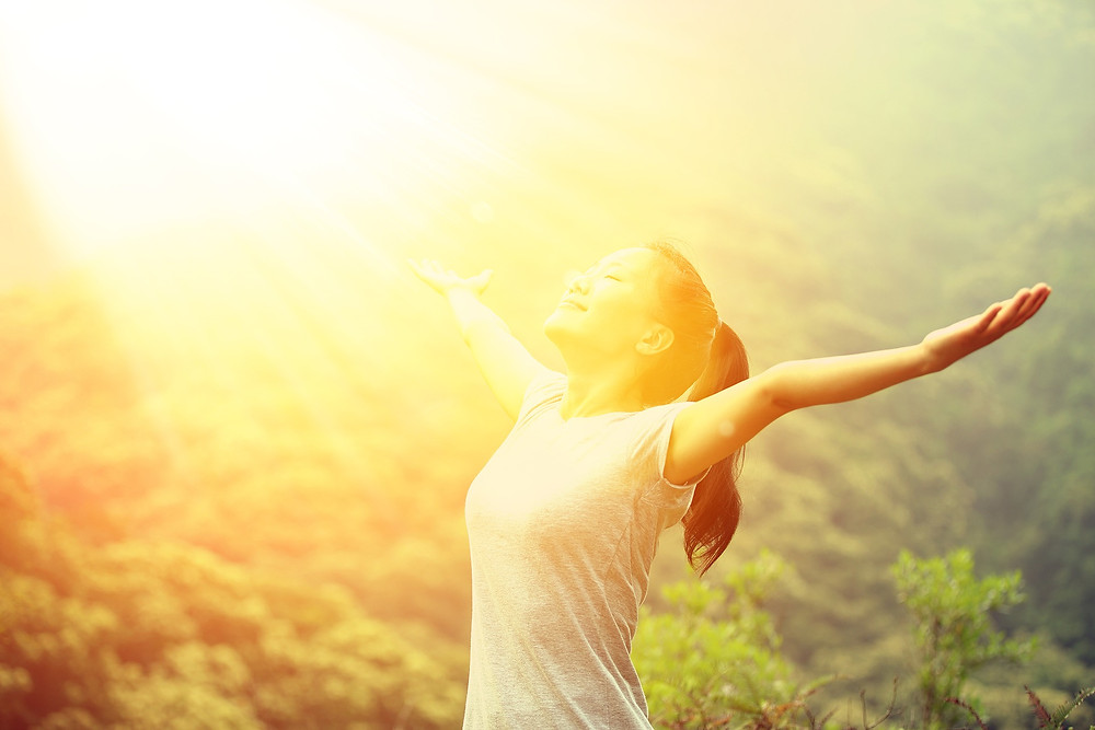 Woman with arms open taking in sunshine