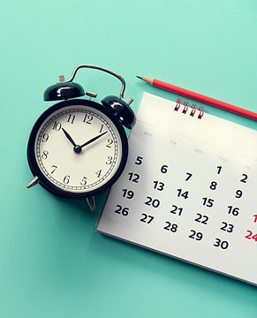 close up of calendar and alarm clock on the green background, planning for business meetin