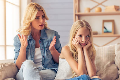 Attractive teenage girl is looking sadly away, leaning on her hands while her mother is sc