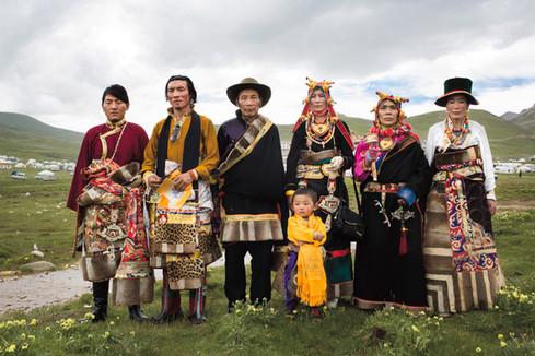 Uma família de tibetanos usa suas melhores roupas tradicionais para a ocasião especial da entronização de seu mestre, o 20º Denma Gonsar Rinpoche. Denma Gonsar Rimpoche Mosteiro Denma Gonsar, Kham, Tibete, julho 31 de 2014.