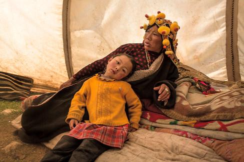 Mãe e filha descansam em sua tenda. A mãe usa um adorno tradicional tibetano feito de âmbar e corais. Monastério Denma Gonsar, Kham, Tibet, 2014
