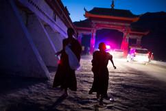 Dois jovens monges deixam a porta do mosteiro no final do último dia de comemorações da entronização de Denma Gonsar Rimpoche. Monastério Denma Gonsar, Kham, Tibet, 2014.
