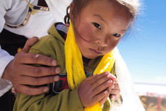 Menina tibetana em oração acompanhada de seu pai, após receber a bênção de Lama Gangchen Rinpoche, o mestre mais importante do mosteiro que veio especialmente para a entronização de Denma Gonsar Rimpoche. Lama Gangchen era amigo íntimo do mestre anterior que faleceu em 2005 e ajudou na busca pelo espírito reencarnado. Mosteiro Denma Gonsar, Kham, Tibet, 2014