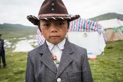 Menino posa em frente à tenda onde sua família está dormindo, para a semana de festividades pela entronização do menino, reconhecido como a reencarnação da curandeiro espiritual Denma Gonsar Rinpoche. Monastério Denma Gonsar, Kham, Tibet, 2014.