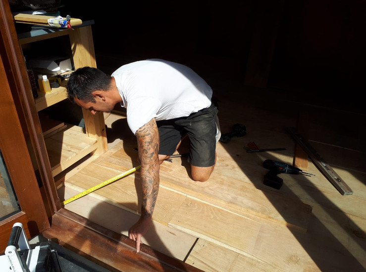 Dan fitting the final piece of flooring