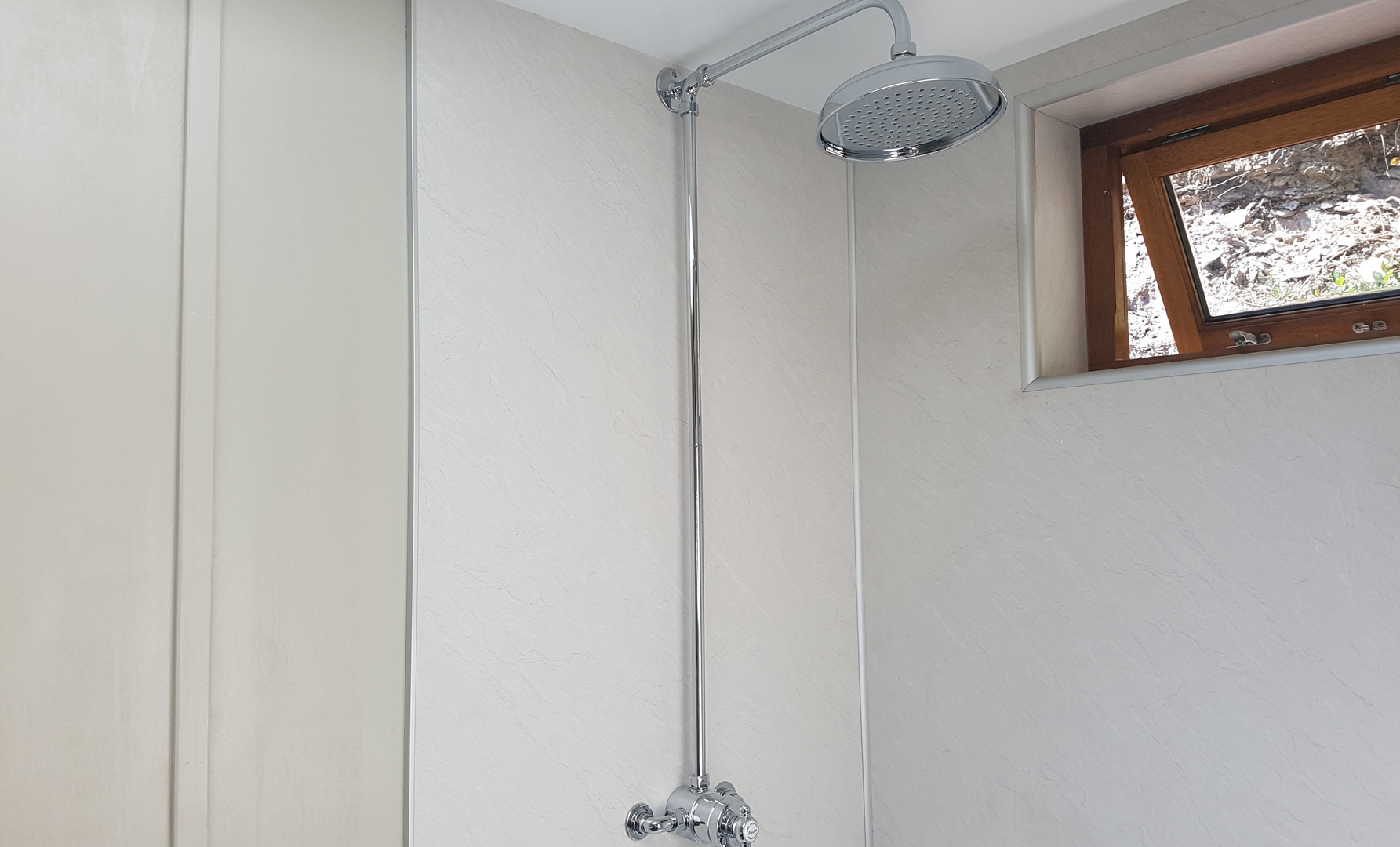 A genorous shower enclosure with a drench shower head