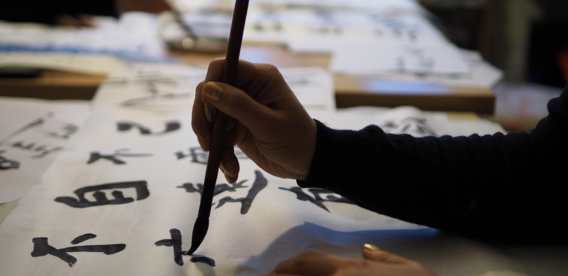 Un pinceau manié avec dextérité lors d'une séance de calligraphie
