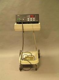 Older cautery machine with a beige cart