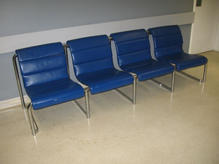 Four attached blue leather chairs