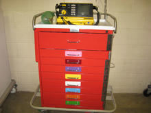 Red crash cart with yellow defibrillator