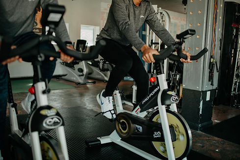 Male in dark grey long sleeved shirt is cycling on a stationary bike in a gym