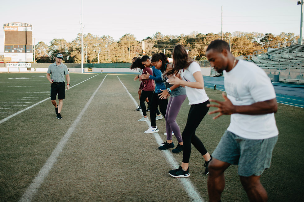 Personal Trainer/Coach leading athletes in line drills on a football field