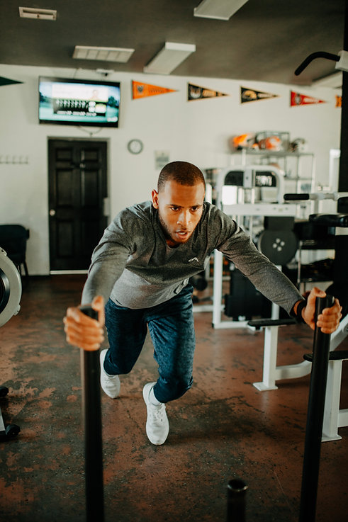 Man in grey long sleeved shirt pushing weighted sled in a gym