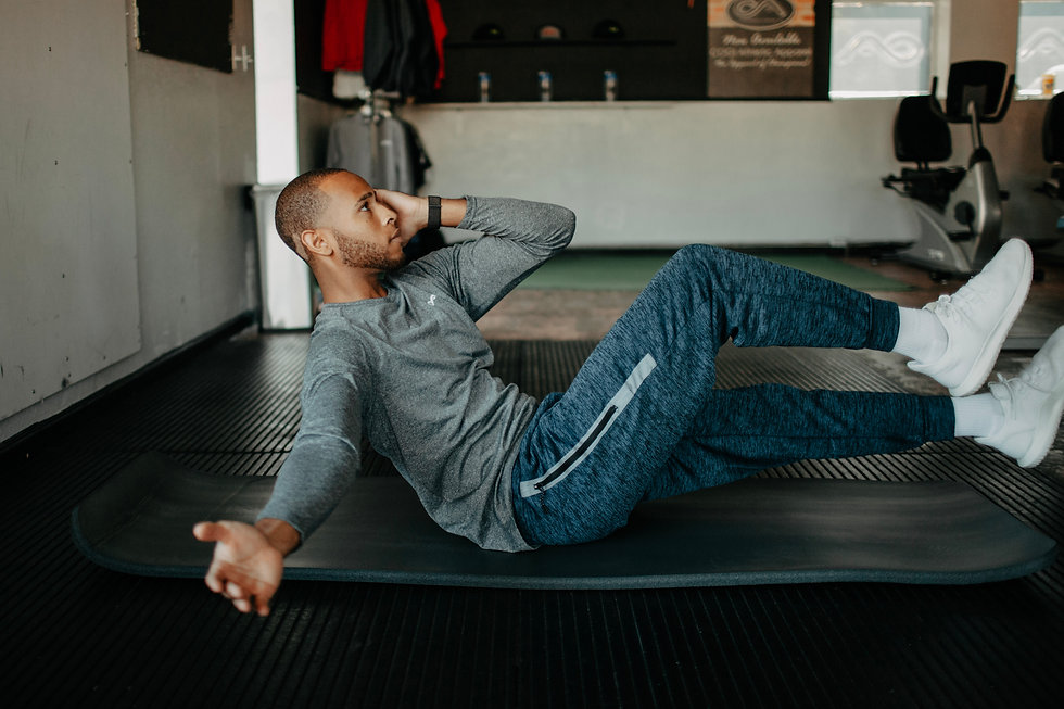 Man in light grey long sleeved shirt performing an abdominal exercise on a mat in a gym