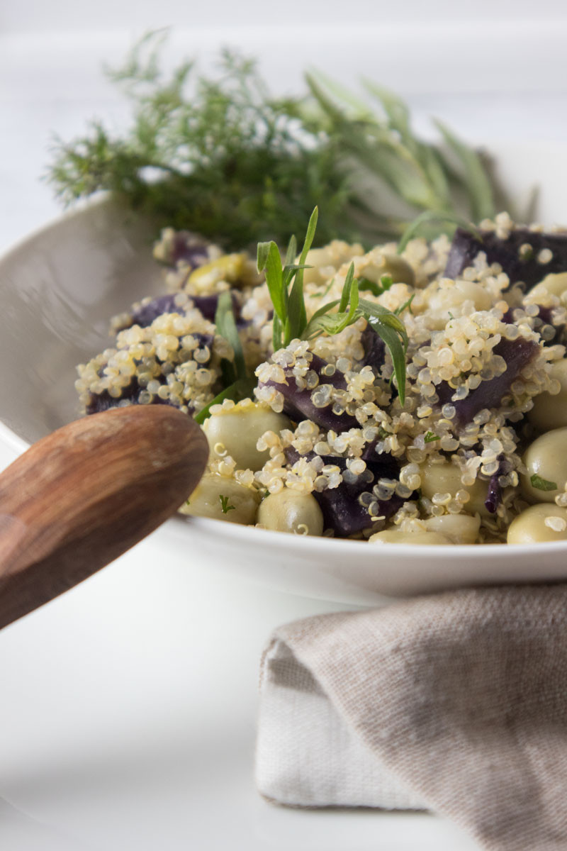Vegan quinoa salad with French beans, herbs and purple potatoes