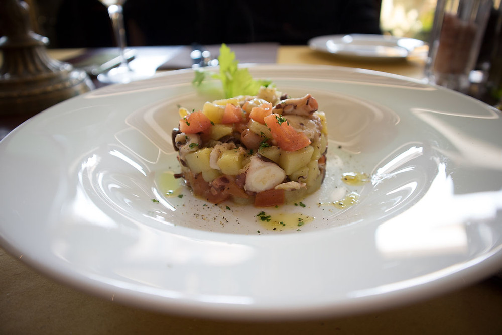 warm octopus salad with potatoes, black taggiasche olives, tomatoes and celery