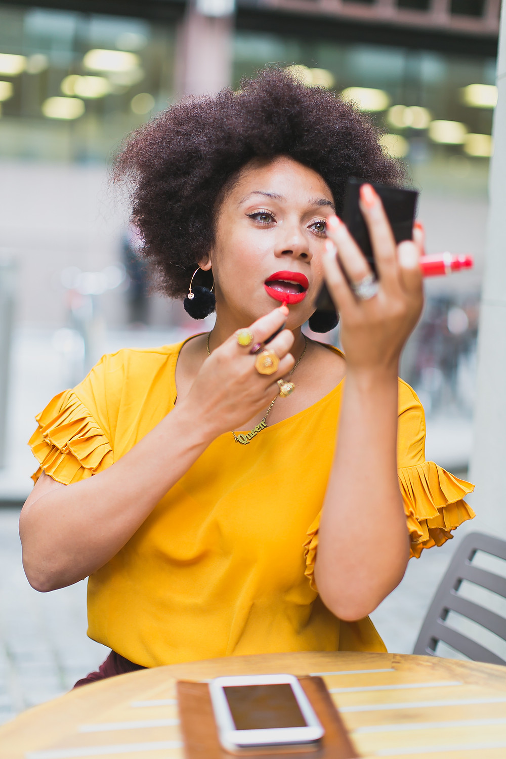 Nat from Style Me Sunday shown sitting at a table wearing a rust coloured top from Avon, pictured applying bright red lipstick. Her hair is work afro style and she has a necklace that spells out queen. She also has big gold rings on too. And Avon black pom pom earrings.