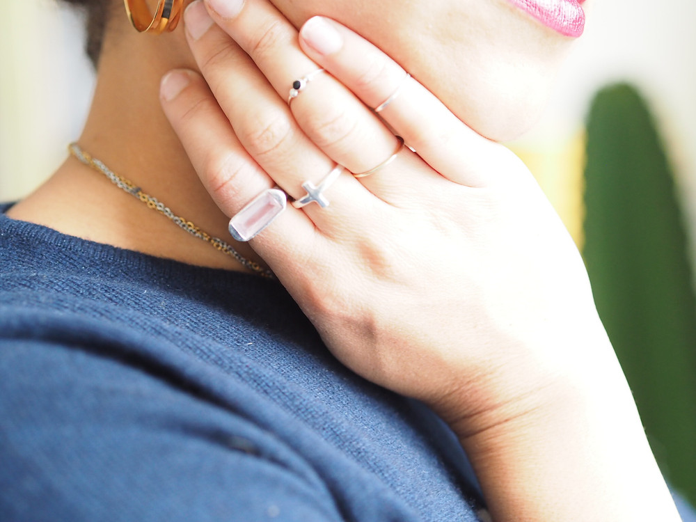Close up of a hand touching the side of a face. Showing Renne jewellery rings