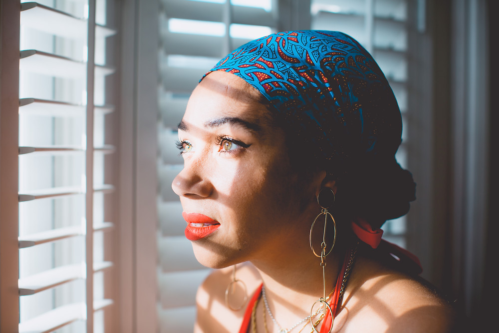 Nat from Style Me Sunday wearing a head scarf from Love Yaa Yaa. Looking out of the window through shutters as the light hits her face.