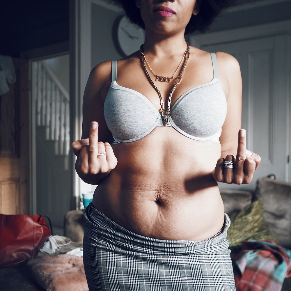 A picture of Nat from Style Me Sunday showing her stomach with stretch marks whilst she holds up her middle fingers.