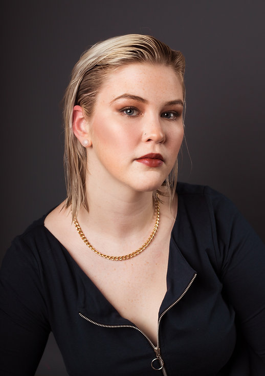 A portrait-style photograph of Sydney Riley with slicked back hair, wearing a blue dress.