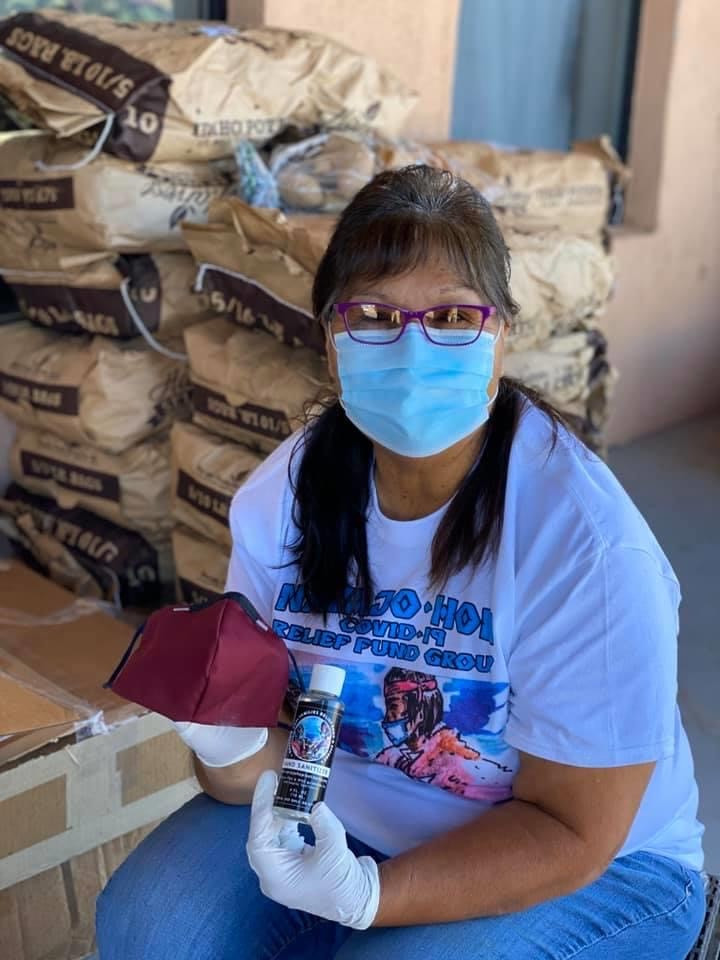 Navajo&Hopi Families COVID-19 Relief Fund Hopi Team Lead, Pamela Lalo, packages food boxes with ppe mask and hand sanitizer that were delivered to the entire village of Orayvi.