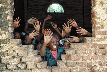 indigenous children waving their hands