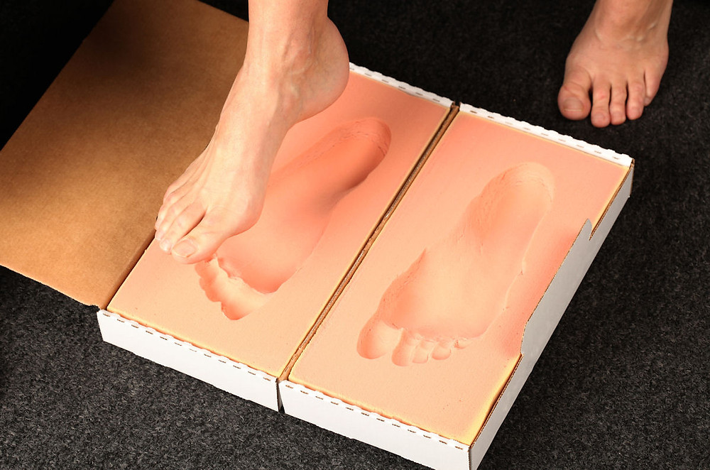 Person stepping into foam casts for orthotics