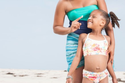 Mom putting sunscreen on daughter