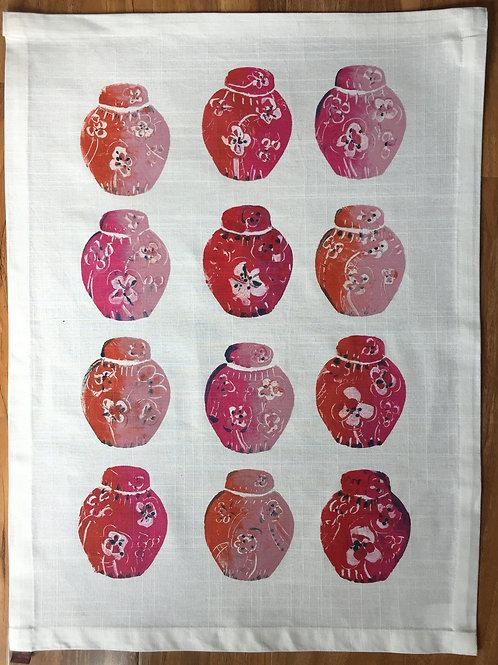 12 pink, red and orange ginger jars on a tea towel