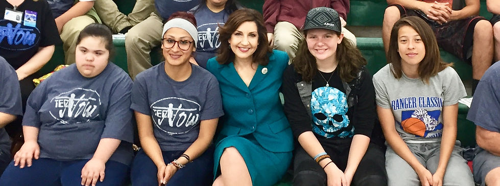 Joy Hofmeister sitting with students.