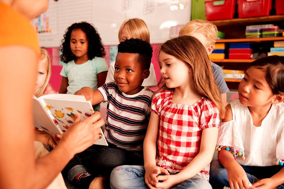 Teacher showing children a book.