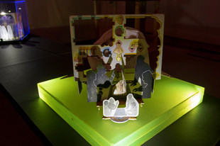 Tableau 8 with tableau 9 partially visible in the backdrop. LED lights, acrylic light box, cuttings and print outs from archive of images collected during research, pieces of readymade 3D paper puzzles, print out of watercolour, glue and black mount board. Dimensions of lightbox: 16.5 in. x 16.5 in. x 3 in.