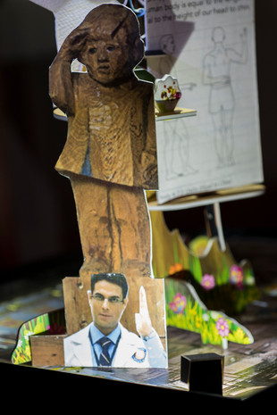 Close up of tableau 2.Image of a saluting child from Marisol Escobar's sculpture 'the Funeral', 1996 and an image of a doctor from a recent Indian ad. Detail of a cut out from a book teaching proportion of the body in drawing (in the background).
