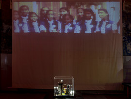 Tableau 7 with looped video projection (8ft. x 3ft.) on the curtain behind. The projection shows schoolgirls swaying from side to side.