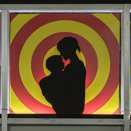 Detail from the facade wall. Cut out silhouette of mother and child. Black mount board, LED lights, designed and printed coloured vinyl sheets. 82.5 cm. x 80 cm.
