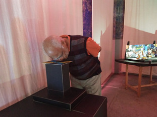 Visitor looking into tableau 5.Black mount board box with mirrors, LED screen, pen drive, remote control, video, glitter paper and glue. Dimensions: 18 in. x 12 in. x 20 in.