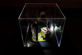 Tableau 7. Dimensions of vitrine: 13.5 in. x 13.5 in. x 12.5 in.LED lights, acrylic vitrine, cuttings and print outs from archive of images collected during research, pieces of readymade 3D paper puzzles, glue and black mount board.