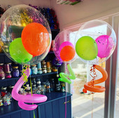 "Neon Baby Shower - Clear 20"" bubbles with neon balloons inside and curly tail."