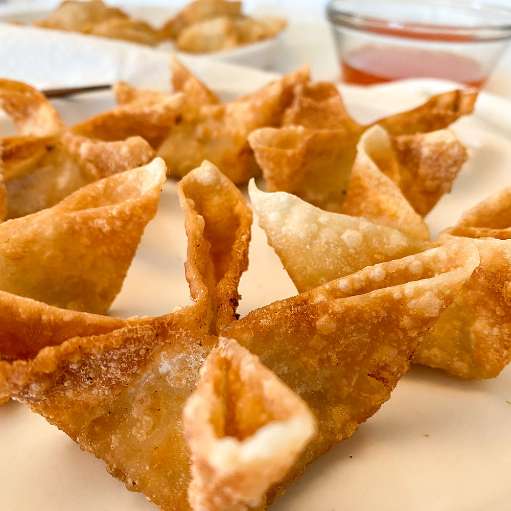 Vegan crab rangoons folded into a flour shape with a side of sweet chili sauce