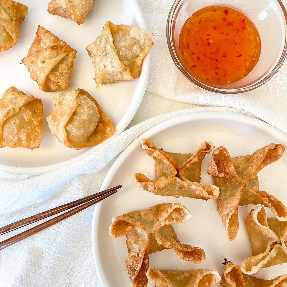Vegan crab rangoons folded two ways with a side of sweet chili sauce