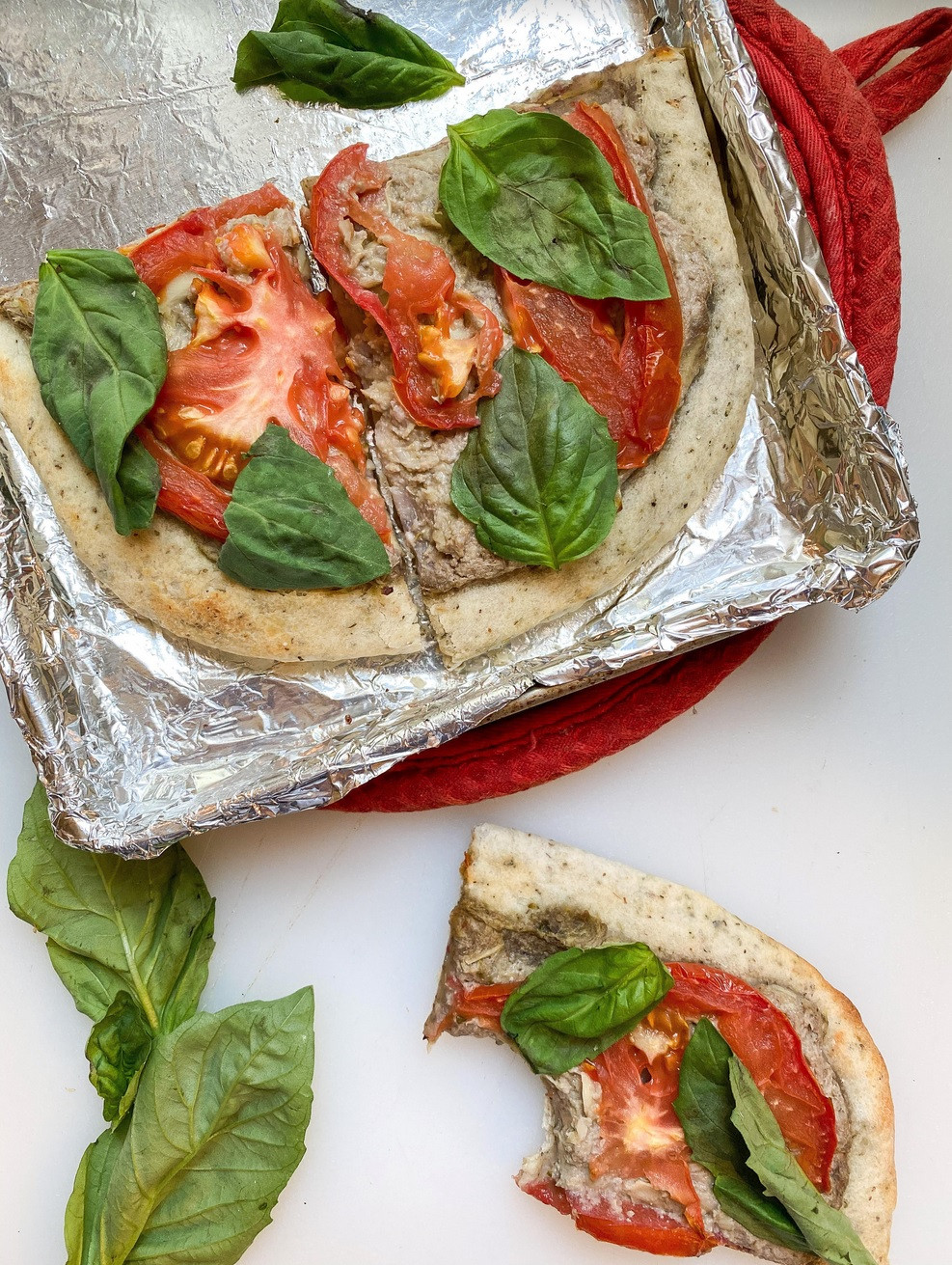 Vegan toaster-oven artichoke pizza, topped with tomato slices and fresh basil