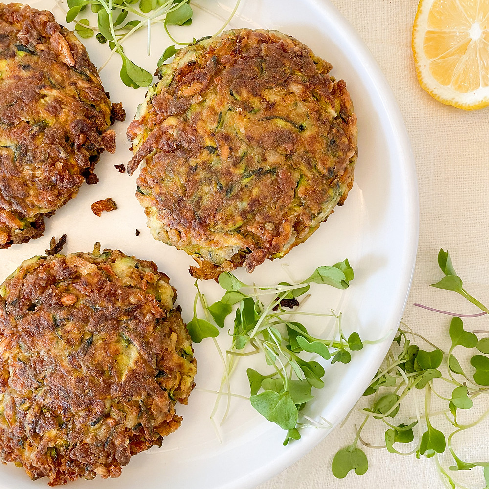 Zucchini crab cakes on a white plate with a side of micro greens and lemon