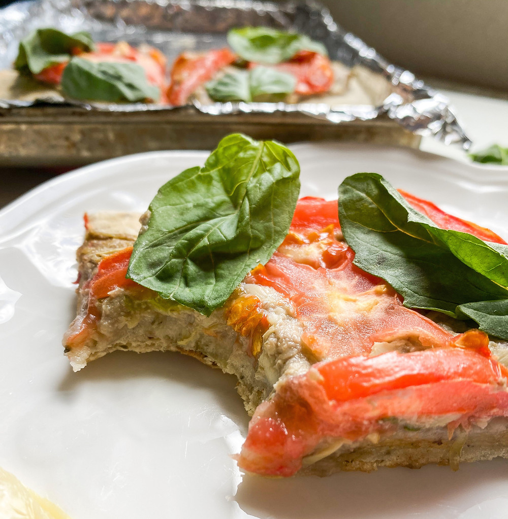 A bite taken out of a slice of vegan toaster-oven artichoke pizza, topped with tomato slices and fresh basil