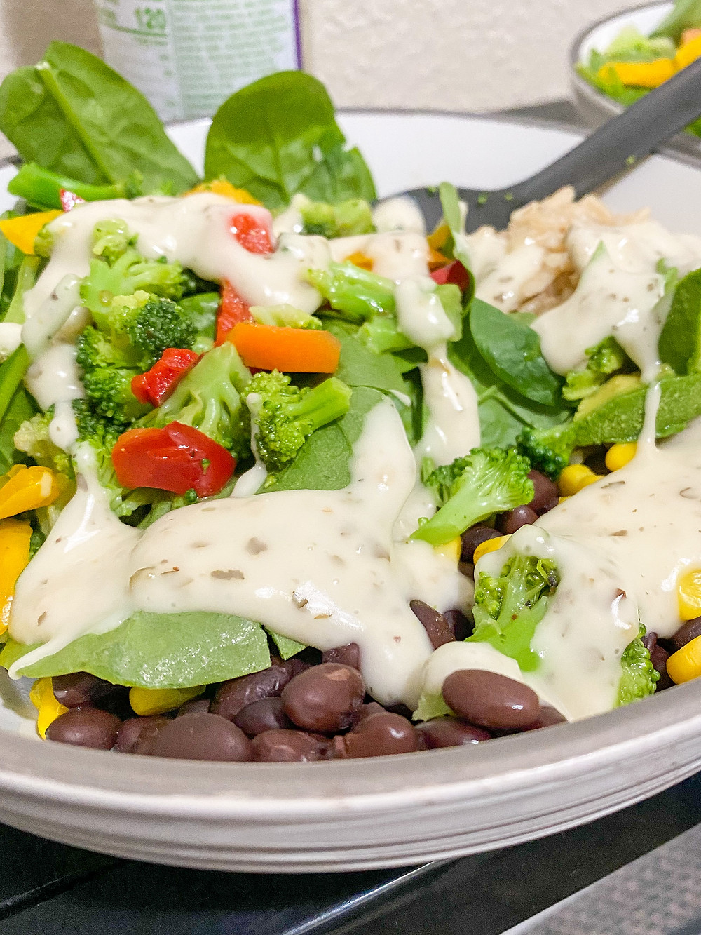 Warm grain salad bowls featuring rice, beans, steamed veggies, corn, avocado, spinach, and ranch dressing.