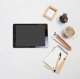 プロモーション動画制作のイメージ画像。ワークデスクにタブレット、ノート(メモ)、コーヒーがあり、これからどんな動画を作ろうか考えているようなイメージ。