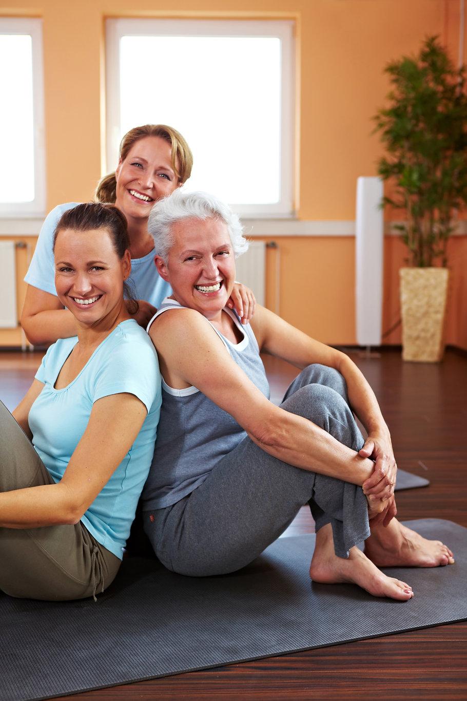 Three happy women sitting in a gym
