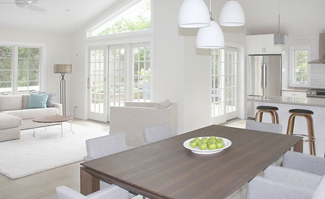 Kitchen design Amagansett with modern wood dining table, counter stools, kitchen renovation, quartz countertop, white kitchen cabinets, gray floors, modern gray dining chairs, pendant fixtures, dining chandelier, stainless steel hood, tile backsplash, interior design Amaganett